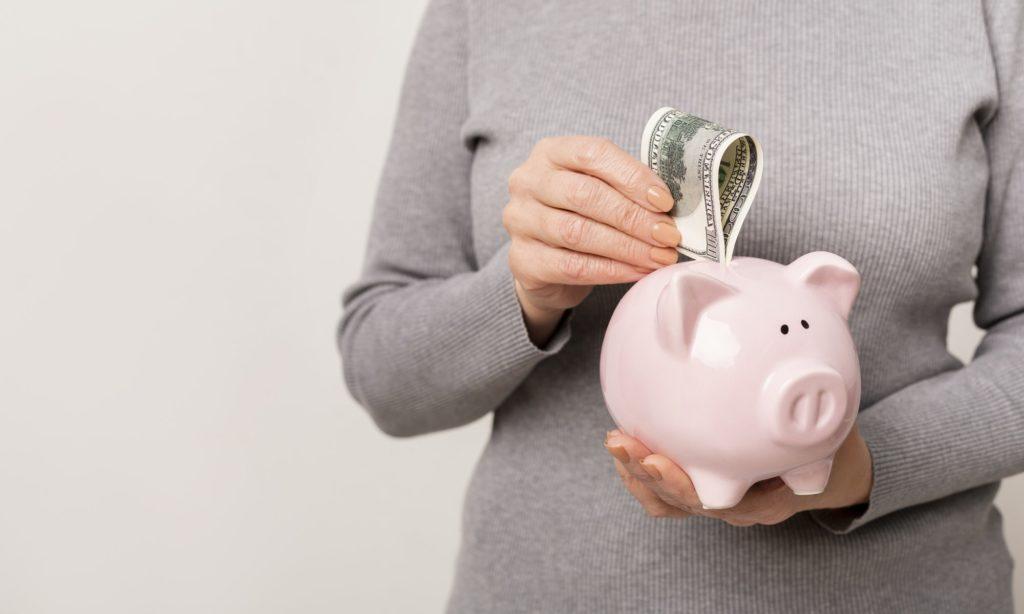 Unrecognizable woman putting cash into piggy bank